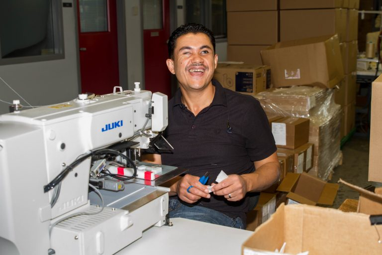 man at sewing machine smiling