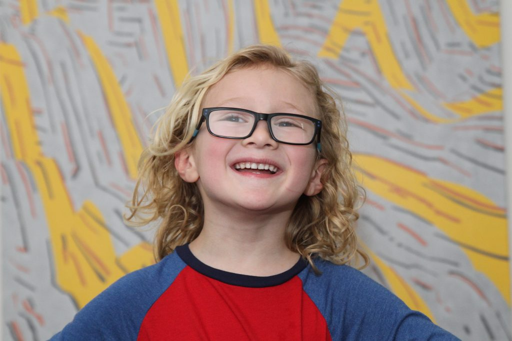 Young boy wearing black glasses and smiling at camera