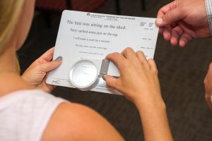 Eye exam - patient reading text using an eye glass magnifier on paper