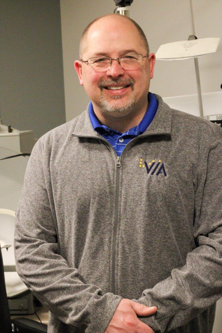 Dr Simmons smiling at the camera wearing a VIA gray sweatshirt