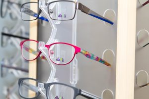 3 pairs of eyeglasses on a clear rack