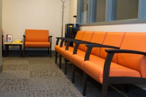 VIA eye clinic waiting room. Bright orange chairs up against a wall.