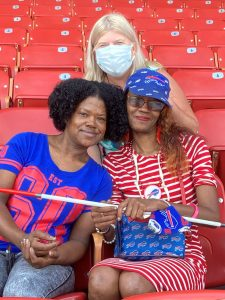 Three women in Buffalo Bills apparel sitting in the stands smiling. One woman (right) has a long cane and Buffalo Bills purse.
