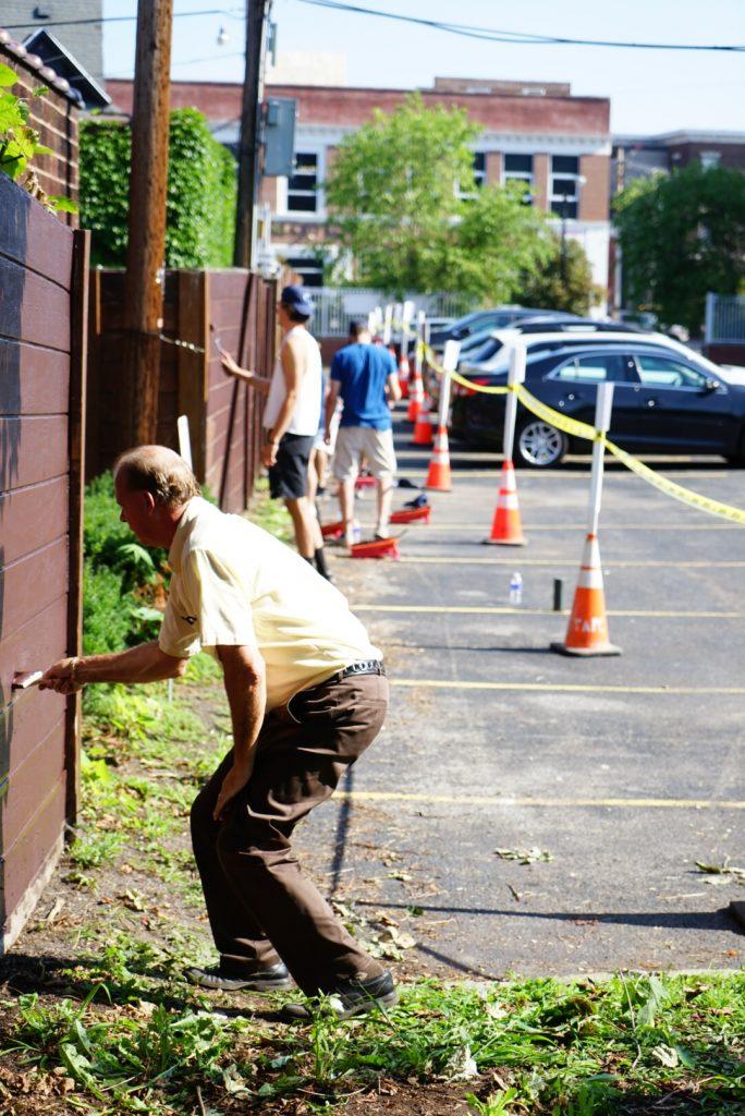 VIA and Bonadio staff painting VIA's fence.