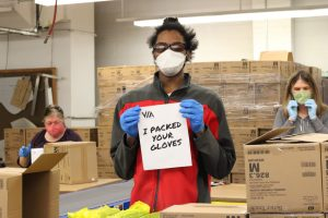 """VIA staff Jordan is packing gloves for Wegmans' distribution. His sign says, """"I packed your gloves."""""""