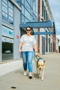 Erica Rodman and her guide dog Jet walking outside of VIA's 1170 Main Street office.