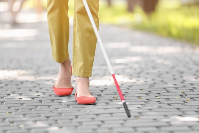 Woman shown from the legs down wearing yellow pants and bright coral shoes walking with a white cane on a sidewalk.