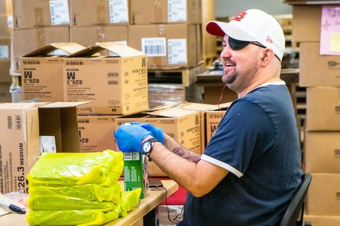 A VIA staff member assembling gloves.