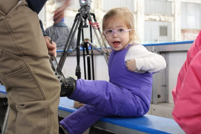 little girl with glasses getting ice skates on