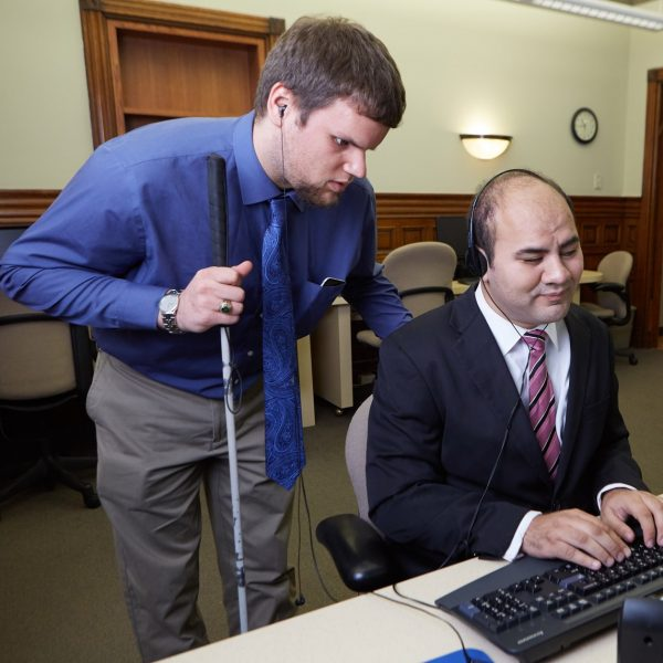 A man with visual impairment is using assistive technology while working on a computer