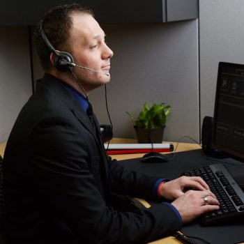 Man wearing headset working at computer in the contact center