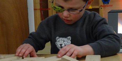 Young boy with glasses on playing with blocks